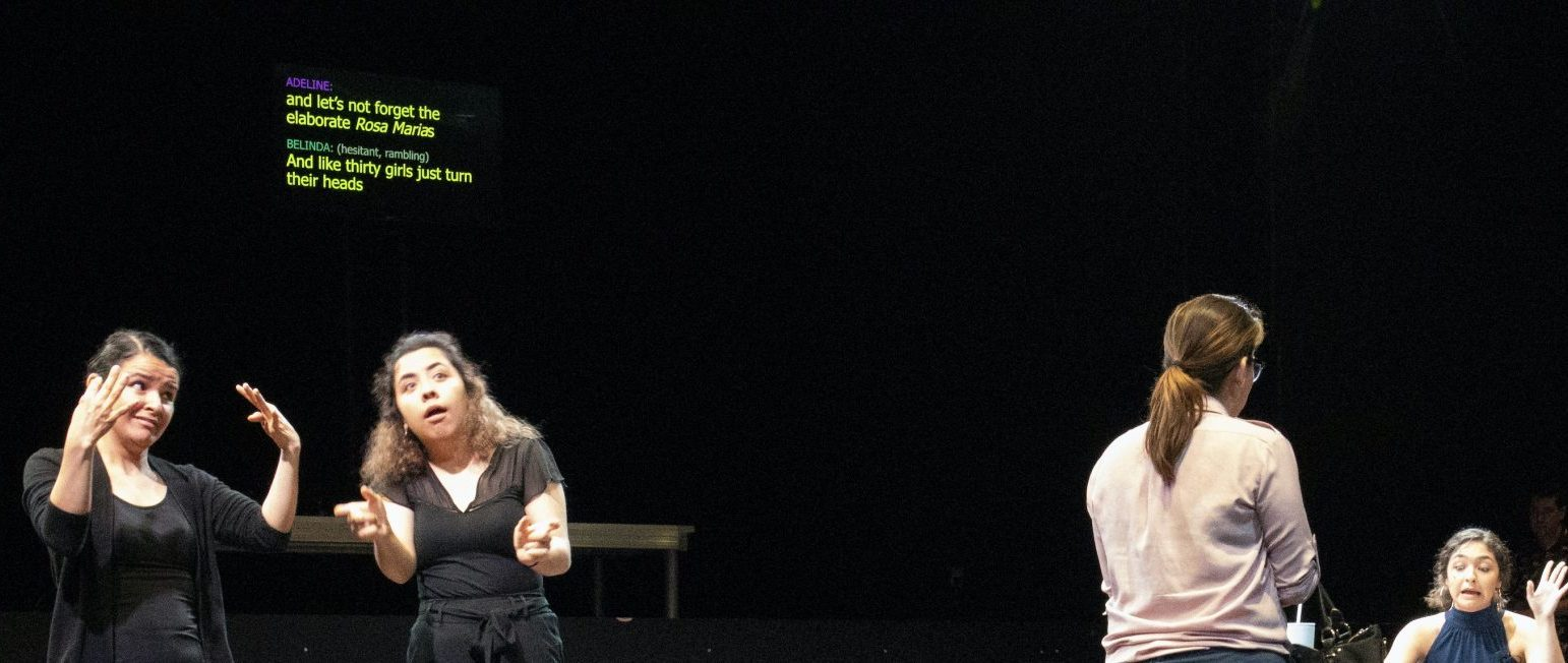 Two ASL interpreters interpret dialogue. In the background is open captioning. To the right two actors perform in a play.